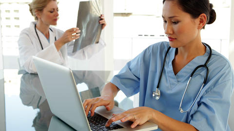 Surgeon using a laptop sitting at table Stock Video Footage