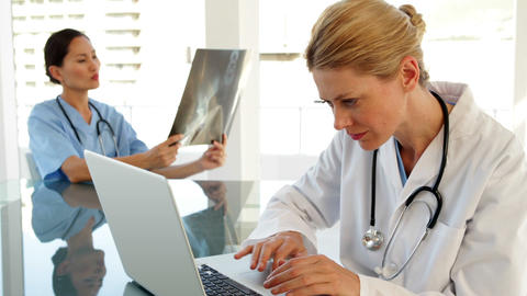 Smiling doctor using a laptop sitting at table Stock Video Footage