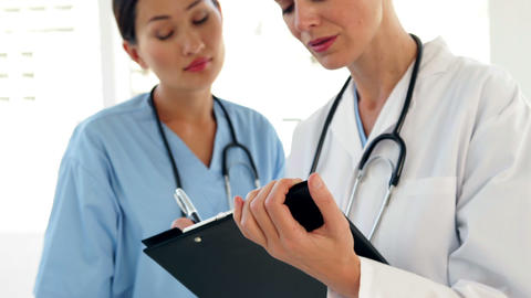 Two doctors looking over a file and smiling at camera Stock Video Footage