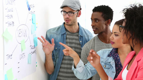 Creative team brainstorming together looking at whiteboard Stock Video Footage