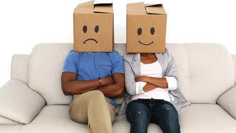 Partners sitting on sofa with emoticon boxes on their heads Stock Video Footage