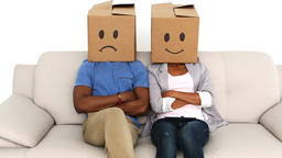 Partners sitting on sofa with emoticon boxes on their heads Footage