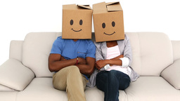 Team sitting on couch with emoticon boxes on their heads Footage