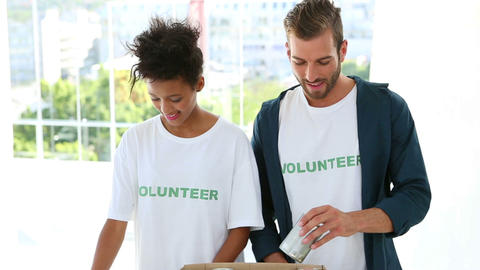 Happy volunteer team packing a food donation box Stock Video Footage