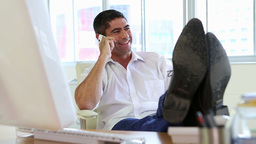 Businessman talking on the phone with feet up on desk Stock Video Footage