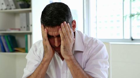 Businessman having a headache at his desk Footage
