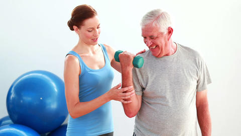 Older man lifting hand weights with the help of his trainer Stock Video Footage