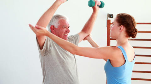 Older man lifting hand weights with the help of his... Stock Video Footage