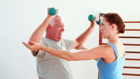 Older man lifting hand weights with the help of his physiotherapist Footage