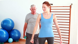 Physiotherapist showing elderly man how to lift weights Stock Video Footage