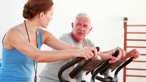 Elderly man using the exercise bike with his trainer Stock Video Footage