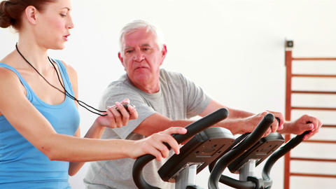 Elderly man using the exercise bike with his trainer Footage