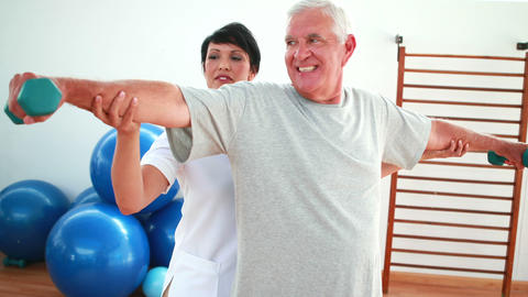 Happy physiotherapist helping elderly patient lift hand weights Footage