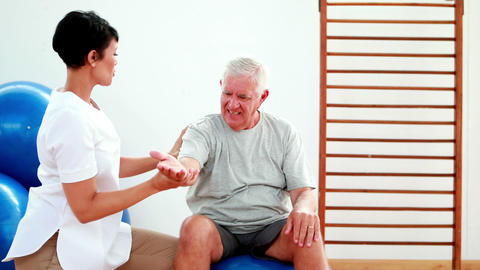 Smiling physiotherapist helping elderly patient stretch arm Stock Video Footage
