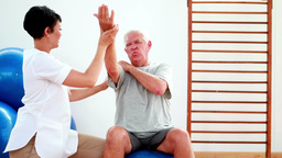 Smiling physiotherapist helping elderly patient stretch arm Footage