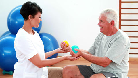 Smiling physiotherapist squeezing massage balls with patient Footage
