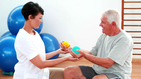 Smiling physiotherapist squeezing massage balls with patient Stock Video Footage