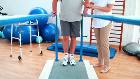 Physiotherapist helping patient walk with parallel bars Stock Video Footage