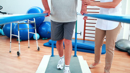 Physiotherapist helping patient walk with parallel bars Footage