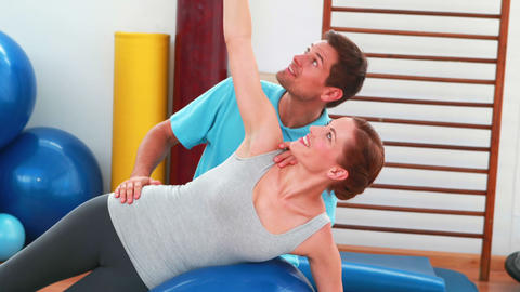 Smiling trainer helping client with side plank position Footage