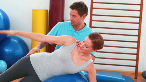 Smiling trainer helping client with side plank position Stock Video Footage