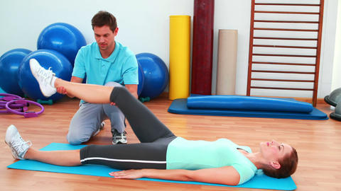 Trainer helping his client bend her knee Stock Video Footage