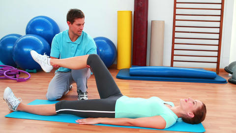 Trainer helping his client bend her knee Footage