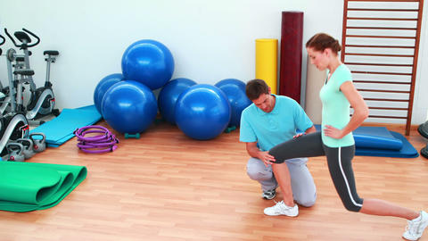 Trainer showing his client how to lunge correctly Stock Video Footage
