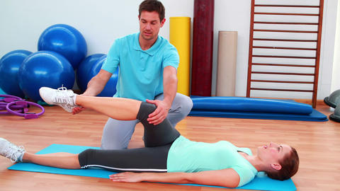 Trainer helping his client bend her leg Stock Video Footage