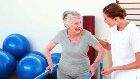 Smiling physical therapist helping patient walk with parallel bars Footage