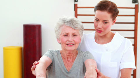 Physical therapist helping patient lift hand weights Stock Video Footage