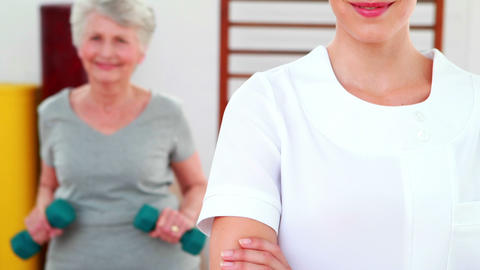 Physical therapist smiling at camera with patient dancing... Stock Video Footage