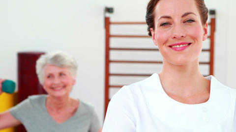 Physical therapist smiling at camera with patient dancing in background Footage