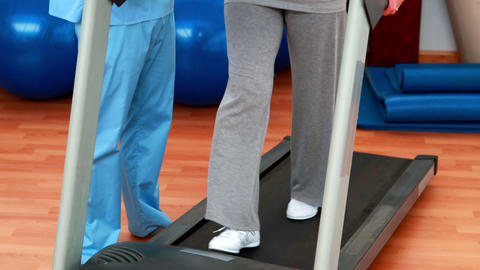 Physical therapist showing patient how to use treadmill Stock Video Footage