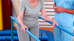 Physical therapist watching patient walk with parallel bars Stock Video Footage