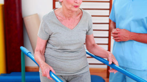 Physical therapist watching patient walk with parallel bars Footage