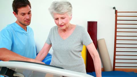 Physical therapist showing patient how to use exercise machine Footage