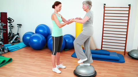 Trainer helping elderly client to use bosu ball Footage