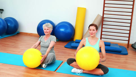 Trainer and elderly client raising exercise balls Stock Video Footage