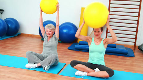 Trainer and elderly client raising exercise balls Footage