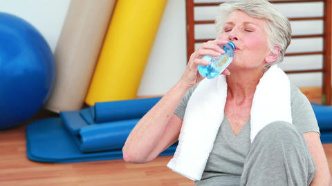 Elderly woman sitting on floor drinking water Footage
