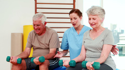 Happy senior citizens exercising with physiotherapist Stock Video Footage
