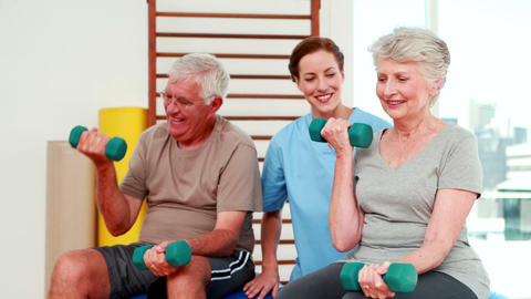 Happy senior citizens exercising with physiotherapist Footage
