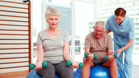 Two senior citizens exercising with physiotherapist Stock Video Footage