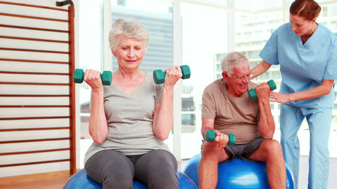 Two senior citizens exercising with physiotherapist Footage