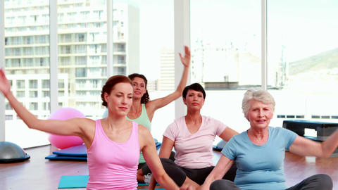 Smiling women doing yoga in fitness studio Stock Video Footage