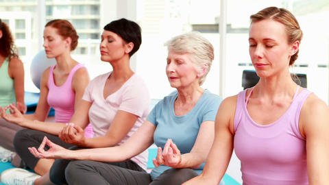 Group of content women in fitness studio doing yoga Stock Video Footage
