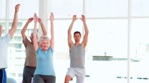 Pilates instructor smiling at camera in front of her class Stock Video Footage