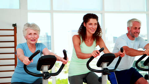 Happy diverse fitness group doing a spinning class Stock Video Footage