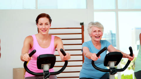 Happy diverse fitness group doing a spinning class Footage
